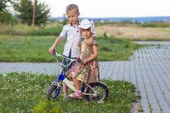 Boy and girl on bicycle playing outdoors on a summer sunny day Stock Photo