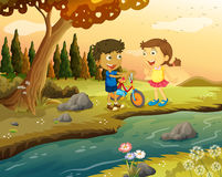 A boy and a girl with a bike standing at the riverbank Stock Photos