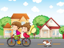 A boy and a girl biking followed by a dog Royalty Free Stock Image