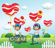 A boy and a girl biking near the giant lollipops Stock Photos