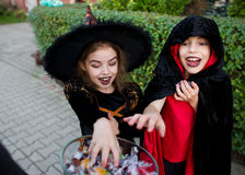 Boy and girl in black suits for Halloween give hands to a vase with sweets. Girl in a suit of the sorcerer and the boy in a black-red cloak of the magician Royalty Free Stock Photos