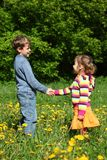 Boy and  girl among blossoming dandelions Stock Images