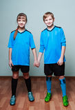 A boy and a girl in blue sporting uniform holding hands Royalty Free Stock Images