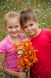 Boy and girl with a bouquet of  lilies Stock Images
