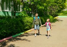 A boy and a girl brother and sister go to school with school bags. Horizontal frame. Selective focus. Copy space. royalty free stock photography