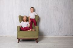 Boy and girl are brother and sister sit on a green armchair royalty free stock images