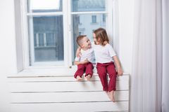 Boy and girl are brother and sister sit on the windowsill at the window stock photo