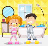 Boy and girl brushing teeth in the bathroom Stock Photos