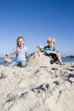 Boy (4-6) and girl (6-8) building sandcastles on sandy beach, smiling, front view, portrait Stock Images