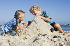 Boy (4-6) and girl (6-8) building sandcastles on sandy beach, smiling, side view Royalty Free Stock Photos