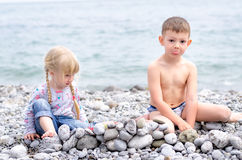 Boy and Girl Building Stone Wall on Rocky Beach Stock Photos