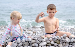 Boy and Girl Building Stone Wall on Rocky Beach Stock Images