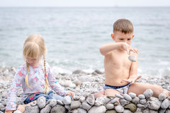 Boy and Girl Building Stone Wall on Rocky Beach Stock Photo