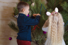 Boy and Girl Busy Decorating a Christmas Tree Royalty Free Stock Images