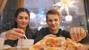 Boy and girl an cafe - drinking tea and eating pizza. Close up stock footage