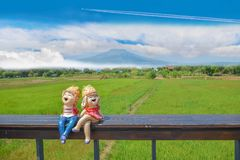 Boy and girl cartoons dolly on wooden seat with the green paddy rice field, the beautiful sky cloud,. Abstract soft focus the boy and girl cartoons dolly on royalty free stock image