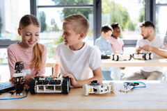 Boy and girl chatting during robotics workshop. Pleasant chat. Pleasant smiling boy talking to his female friend while constructing a robotic vehicle together Stock Images