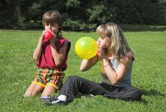 Boy and girl cheats varicolored air-ball. In solar daytime Royalty Free Stock Photos