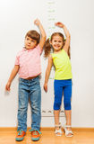 Boy and a girl check height on wall scale Royalty Free Stock Photo