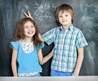 Boy and girl children indulge in school. Children indulge in a lesson about the school board royalty free stock images