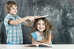 Boy and girl children indulge in school. Children indulge in a lesson about the school board stock photo