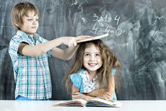 Boy and girl children indulge in school. Children indulge in a lesson about the school board stock image