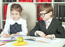 Boy and girl children indulge in school. Boy and girl sitting at a table in the schoolchildren with books, pencils, prepare homework in school stock photo
