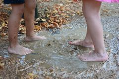 CHILDREN LEGS PLAYING IN A MUD PUDDLE ON SUMMER royalty free stock images