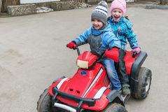 Boy girl children`s ride on a double Quad bike. They are dressed in pants, jackets and caps. Stock Images