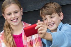 Boy and Girl Children Taking Cell Phone Selfie Stock Images