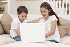 Boy & Girl Children Using Laptop Computer at Home. Young boy & girl children using laptop computer on a sofa at home Royalty Free Stock Photography