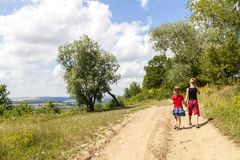 A boy and a girl children walk on a dirt road on a sunny summer day. Kids holding hands together while enjoying ativity outdoors. Royalty Free Stock Photo