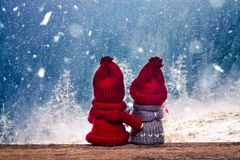 Boy and girl christmas dolls in winter wonderland watching snowy. Boy and girl christmas dollsin winter wonderland watching snowy fir trees in the mountains royalty free stock image