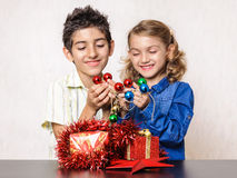 Boy and girl with Christmas present and decorations Royalty Free Stock Image