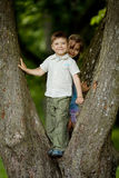 Boy and girl climb big tree Stock Photo