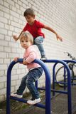 Boy and girl climb on bike parking. Little boy and girl climb on bike parking royalty free stock image