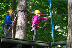 Boy and girl  climbing in adventure park Stock Photo