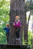 Boy and girl  climbing in adventure park Stock Images