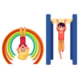 Boy and girl climbing, hanging on monkey bars at playground Royalty Free Stock Images