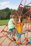 Boy and girl climbing on ropes. Toddler boy and girl climbing on ropes of a equipment on a playground in the summer on August 2017 in Poznan, Poland Royalty Free Stock Photos