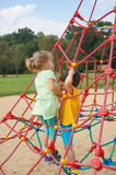 Boy and girl climbing on ropes. Toddler boy and girl climbing on ropes of a equipment on a playground in the summer on August 2017 in Poznan, Poland Stock Photo