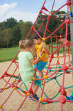 Boy and girl climbing on ropes. Toddler boy and girl climbing on ropes of a equipment on a playground in the summer on August 2017 in Poznan, Poland Stock Images