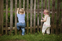 Boy and girl climbs the fence Royalty Free Stock Photos