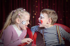 Boy and Girl Clowns Sticking Out Tongues. Boy and Girl Wearing Clown Make Up Sitting Side by Side and Sticking Tongues Out at Each Other Stock Image