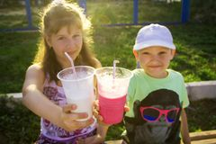 Boy and girl with cocktails in hands stock images