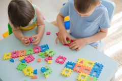 A boy and a girl collect a soft puzzle at the table. Brother and sister have fun playing together in the room. Preschool children and educational toys stock images