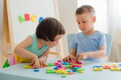 A boy and a girl collect a soft puzzle at the table. Brother and sister have fun playing together in the room. Preschool children and educational toys stock photo