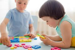 A boy and a girl collect a soft puzzle at the table. Brother and sister have fun playing together in the room. Preschool children and educational toys royalty free stock photo