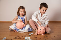 Boy and girl collecting money in the piggy bank Royalty Free Stock Photography