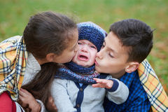 Boy and girl comforting crying brother Stock Image